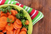 Slices of carrot, sorrel and parsley in green round bowl on napkin on wooden background