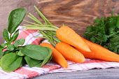 Carrots, dill and parsley on napkin on cutting board on wooden background
