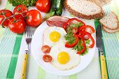 Scrambled eggs with bacon and vegetables served on plate on fabric background