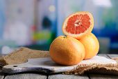 Ripe grapefruits on cutting board, on wooden table, on bright background