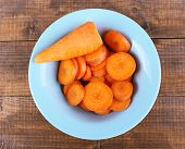 Slices of carrot in blue round bowl on wooden background