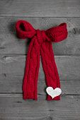 Red Knitted Bow With White Heart On Wooden Background For Christmas, Valentine, Birthday Or Mother's