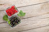 Fresh ripe currant berries on wooden table background with copy space
