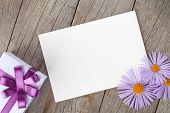 Photo frame with gift box and gerbera flowers over wooden table background