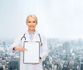 healthcare and medicine concept - smiling female doctor with stethoscope pointing finger to clipboar