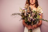 picture of condolence  - A young woman is holding a bouquet of dead flowers  - JPG