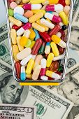tablets, shopping cart, dollar bills, symbolic photo for pharmaceuticals, health insurance, health c
