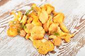 stock photo of chanterelle mushroom  - Chanterelle mushroom on textured vintage wooden background - JPG
