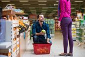 stock photo of department store  - Beautiful Young Couple Shopping For Fruits And Vegetables In Produce Department Of A Grocery Store - Supermarket - Shallow Deep Of Field