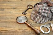 foto of sherlock  - Sherlock Holmes Cap famous as Deerstalker Old Key Real Handcuffs and Vintage Magnifying Glass on Grunge Wooden Table - JPG