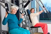 foto of retirement age  - Happy Elderly Women Working Out at the Fitness Gym While Looking at the Camera - JPG