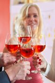 Hands Tossing Red Wine On Elegant Glasses