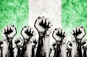picture of labor  - Nigeria Labor movement graphic concept workers union strike concept with male fists raised in the air fighting for their rights and Nigerian national flag in out of focus background - JPG