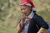 Lady in traditional Red Dzao hill tribe dress eats fruit in Sapa, Vietnam.