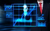 Businessman Drawing Arrows And Graph