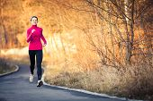 Young woman running outdoors in a city park on a cold fall/winter day