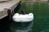 picture of outboard engine  - white inflatable tender tied down at a pier with outboard engine - JPG