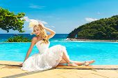 stock photo of infinity pool  - Beautiful young bride in a wedding dress sitting on the edge of the infinity - JPG