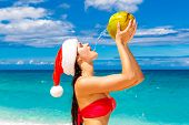 Young Beautiful Woman With Long Black Hair In Red Bikini, Dressed In Red Santa Claus Hat