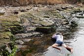 stock photo of accident victim  - View of a young woman washed up on rocks at the edge of a river possible boating accident victim - JPG