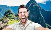 Happy young man taking a selfie photo in Macchu Picchu, Peru