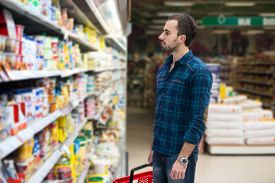 pic of department store  - Handsome Young Man Shopping For Fruits And Vegetables In Produce Department Of A Grocery Store  - JPG