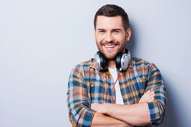 stock photo of adults only  - Handsome young man wearing headphones on his neck and smiling while standing against grey background - JPG