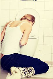 picture of vomiting  - Young caucasian woman is vomiting in the bathroom - JPG