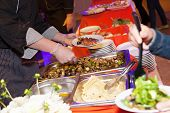 stock photo of catering  - Hands of cook serving food at a catered event - JPG