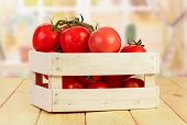 stock photo of crate  - Fresh tomatoes in wooden crate on kitchen table - JPG