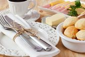 stock photo of brazilian food  - Brazilian snack pao de queijo (cheese bread) on white plate with butter cheese ham cup of coffee on wooden table. Selective focus ** Note: Shallow depth of field - JPG