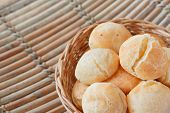 picture of brazilian food  - Brazilian snack cheese bread (pao de queijo) in wicker basket on wooden table. Selective focus. Copy space ** Note: Shallow depth of field - JPG