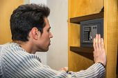 image of vault  - Young handsome man using a small vault or safe in his home - JPG