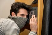 picture of vault  - Young male burglar hiding face with mask opening a small home vault or safe - JPG