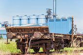 image of wagon  - Railway freight wagon with a factory in the background - JPG