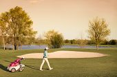 stock photo of golf bag  - Woman golf player walking during sunset with golf bag at beautiful fairway with lake and bunker in background - JPG