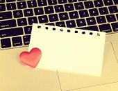 picture of pegging  - Laptop keyboard with small red hearts clothes pegs and sticky note - JPG