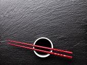 stock photo of soy sauce  - Japanese sushi chopsticks over soy sauce bowl on black stone background - JPG