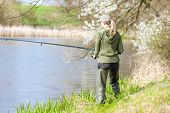 stock photo of woman boots  - woman fishing at pond in spring - JPG