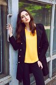 picture of blouse  - Young woman in black trenchcoat and a yellow blouse - JPG