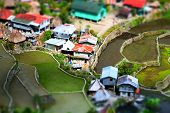 picture of tilt  - Amazing tilt shift effect view of rice terraces fields and village houses in Ifugao province mountains - JPG