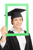 stock photo of graduation gown  - Vertical shot of a female student posing in graduation gown behind a green picture frame isolated on white background - JPG