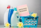 picture of detergent  - Detergent with washing powder and towels in basket on pale background - JPG