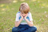 stock photo of sad boy  - Little boy feeling sad in the park on a sunny day - JPG