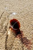 stock photo of glass-wool  - A glass of red wine spilt on a wool carpet - JPG