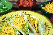 A Dish Of Tacos And Bowls Of Toppings