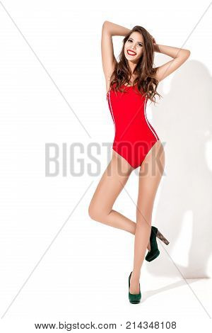poster of slim smiling brunette woman in a red swimsuit and high heels against a white wall