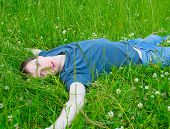 The Young Man Lies On A Green Grass