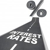 The words Interest Rates on a blacktop road and a percent sign at the top of the street, symbolizing the rising interest rates due to economic factors and conditions