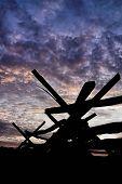 foto of split rail fence  - A wooden split rail fence precedes darkness under a dramatic sunset sky - JPG